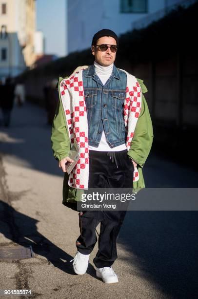 Alex Badia wearing denim jacket black velvet pants beanie white sneakers green jacket is seen outside Diesel during Milan Men's Fashion Week...