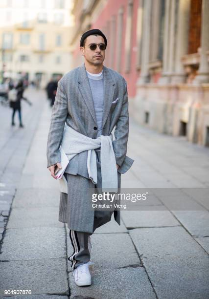 Alex Badia wearing grey wool coat knit track suit pants white sneakers is seen outside MSGM during Milan Men's Fashion Week Fall/Winter 2018/19 on...