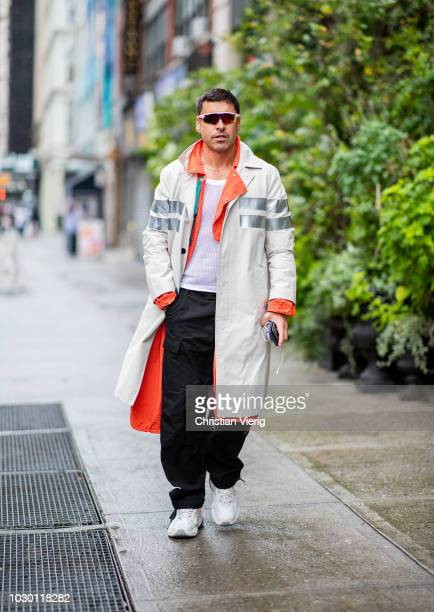 Alex Badia wearing orange and creme white trench coat is seen outside Brock Collection during New York Fashion Week Spring/Summer 2019 on September 9...