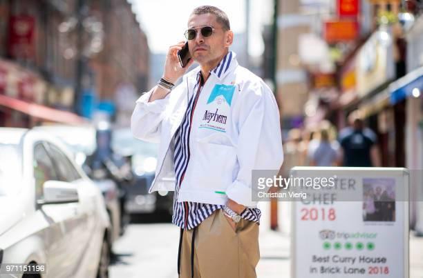 Alex Badia wearing striped button shirt white jacket is seen during London Fashion Week Men's June 2018 on June 10 2018 in London England