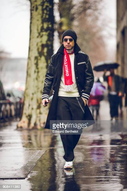Alex Badia wears a beanie hat sunglasses a redd scarf Nothing print a bomber jacket a white top sneakers under the rain outside Paul Smith during...