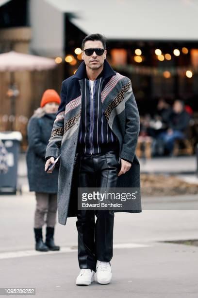 Alex Badia wears a Fendi gray striped coat a striped shirt black leather pants white sneakers outside Acne Studios during Paris Fashion Week Menswear...