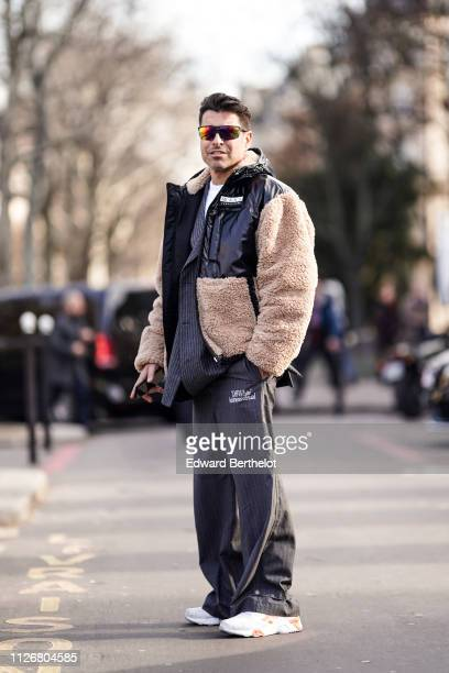 Alex Badia wears sunglasses a black padded jacket where is the inscription Wang competition with beige fauxfur pockets and sleeves a grey striped...