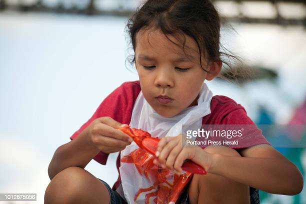 Alex Baptista of Ayer Mass picked apart a lobster during the children's lobster eating contest at the Maine Lobster Festival in Rockland on Sunday...