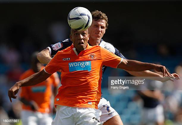 Alex Baptiste of Blackpool heads the ball under pressure from Darius Henderson of Millwall during the npower Championship match between Millwall and...