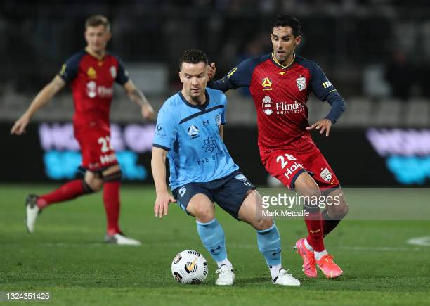 Alex Baumjohann of Sydney FC is pressured by Juande of Adelaide United during the A-League Semi-Final match between Sydney FC and Adelaide United at...