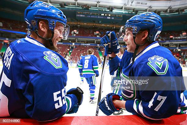 Alex Biega and Sven Baertschi of the Vancouver Canucks talk on from the bench during their NHL game against the Boston Bruins at Rogers Arena...