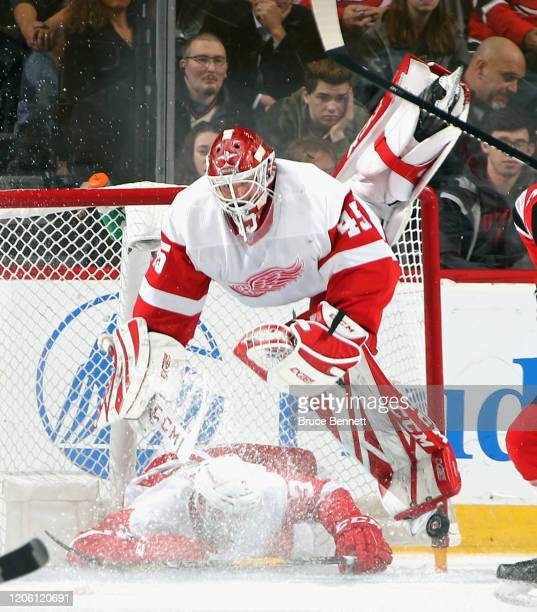 Alex Biega of the Detroit Red Wings slides into Jonathan Bernier during the third period against the New Jersey Devils at the Prudential Center on...