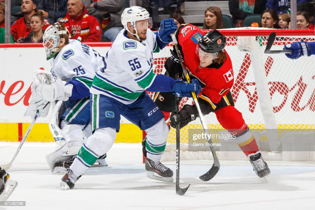Alex Biega #55 of the Vancouver Canucks and Mark Jankowski #77 of the Calgary Flames battle for position in an NHL game against the Vancouver Canucks at the Scotiabank Saddledome on November 7, 2017 in Calgary, Alberta, Canada.