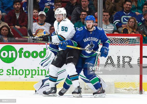 Alex Biega of the Vancouver Canucks checks Chris Tierney of the San Jose Sharks during their NHL game at Rogers Arena March 17 2018 in Vancouver...