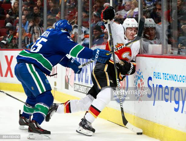 Alex Biega of the Vancouver Canucks checks Matthew Tkachuk of the Calgary Flames into the boards during their NHL game at Rogers Arena December 17...