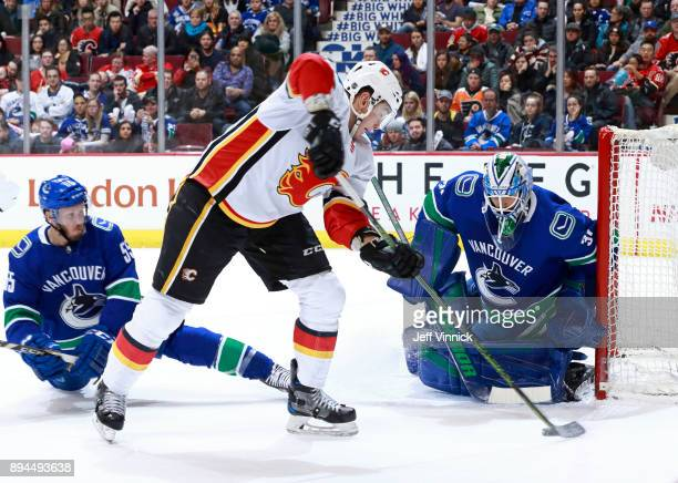 Alex Biega of the Vancouver Canucks looks on a Micheal Ferland of the Calgary Flames takes a shot on Anders Nilsson of the Vancouver Canucks during...