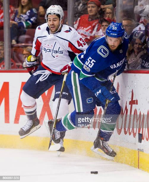 Alex Biega of the Vancouver Canucks picks up the loose puck after avoiding a hit from Tom Wilson of the Washington Capitals in NHL action on October...