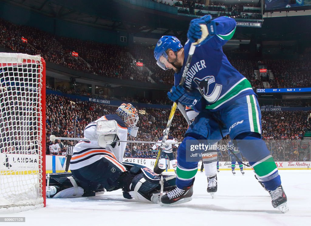 Alex Biega #55 of the Vancouver Canucks takes a shot against Cam Talbot #33 of the Edmonton Oilers during their NHL game at Rogers Arena March 29, 2018 in Vancouver, British Columbia, Canada. Vancouver won 3-1.