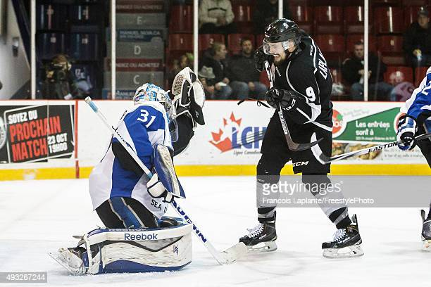 Alex Bishop of the Saint John Sea Dogs makes a glove save as Yan Pavel Laplante of the Gatineau Olympiques looks for a rebound on October 18 2015 at...