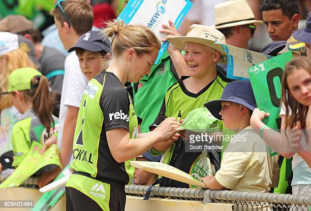 Alex Blackwell of the Thunder signs autographs for supporters in the crowd after the Women's Big Bash League match between the Melbourne Stars and...