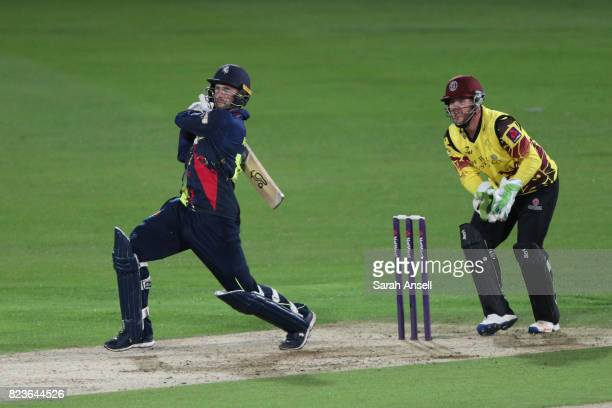 Alex Blake of Kent Spitfires hits a boundary as Somerset wicket keeper Steven Davies looks on during the NatWest T20 Blast South Group match at The...