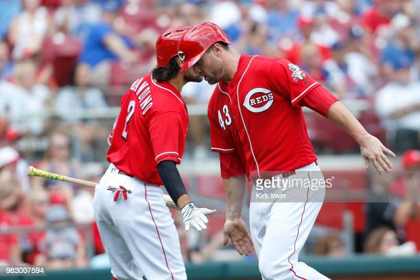 Alex Blandino of the Cincinnati Reds congratulates Scott Schebler after scoring the go ahead run during the seventh inning of the game against the...