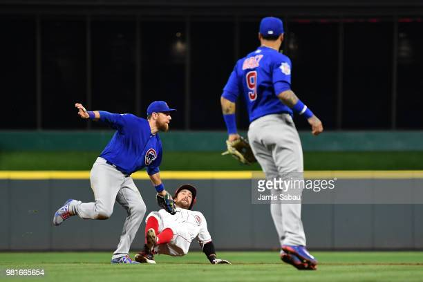 Alex Blandino of the Cincinnati Reds is tagged out between first and second bases by Ben Zobrist of the Chicago Cubs after trying to extend a single...
