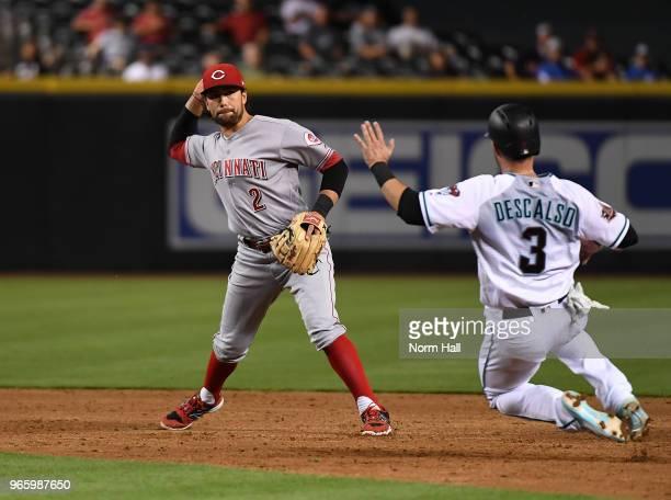 Alex Blandino of the Cincinnati Reds turns a double play as Daniel Descalso of the Arizona Diamondbacks slides into second base during the third...