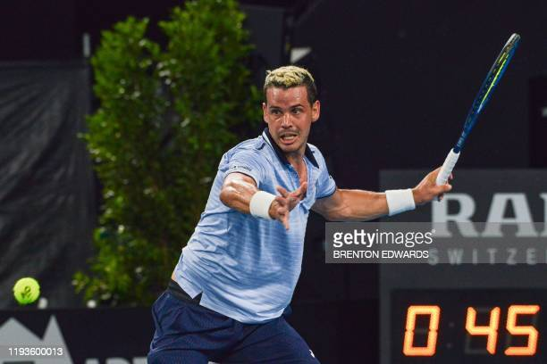Alex Bolt of Australia hits a return to Stephane Robert of France during their men's first round singles match at the Adelaide International tennis...