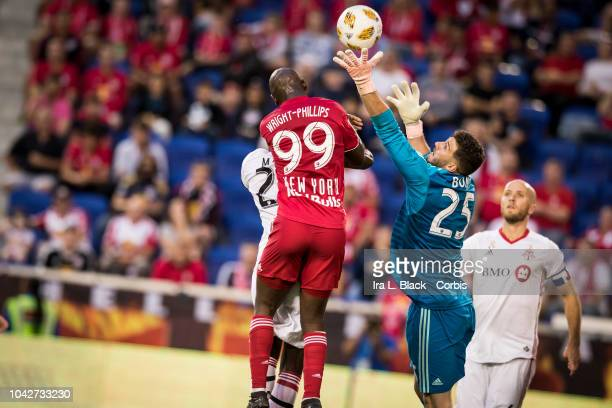 Alex Bono of Toronto FC jumps up for the ball to stop the advance by Bradley WrightPhillips of New York Red Bulls during the Major League Soccer...