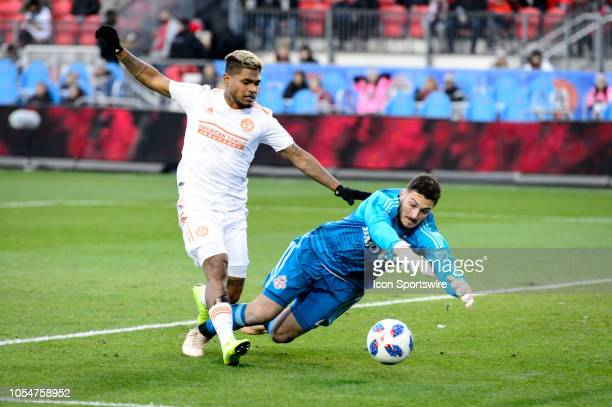 Alex Bono of Toronto FC stops a dribble attempt by Josef Martinez of Atlanta United FC during the first half of the MLS Decision Day match between...