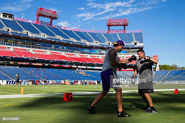Alex Boone and coach Jeff Hurd of the Minnesota Vikings warm up by boxing before the first game of the season against the Tennessee Titans at Nissan...