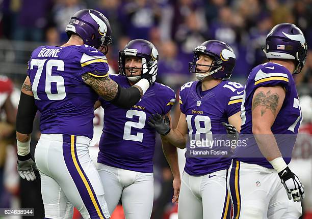 Alex Boone of the Minnesota Vikings celebrates with kicker Kai Forbath and Jeff Locke after a successful extra point try in the first quarter of the...