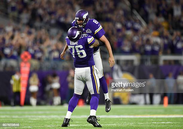 Alex Boone of the Minnesota Vikings celebrates with quarterback Sam Bradford after a touchdown pass in the third quarter of the game on against the...