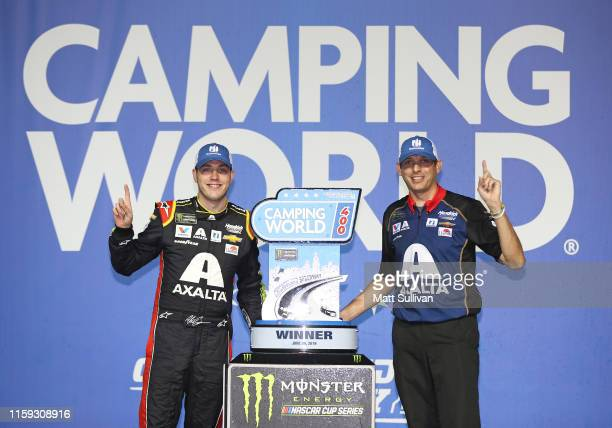 Alex Bowman driver of the Axalta Chevrolet and crew chief Greg Ives pose with the trophy after winning the Monster Energy NASCAR Cup Series Camping...