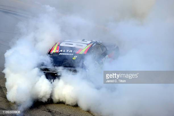 Alex Bowman driver of the Axalta Chevrolet celebrates with a burnout after winning the Monster Energy NASCAR Cup Series Camping World 400 at...