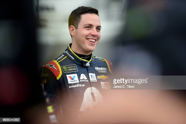 Alex Bowman driver of the Axalta Chevrolet stands by his car during qualifying for the Monster Energy NASCAR Cup Series Coke Zero Sugar 400 at...