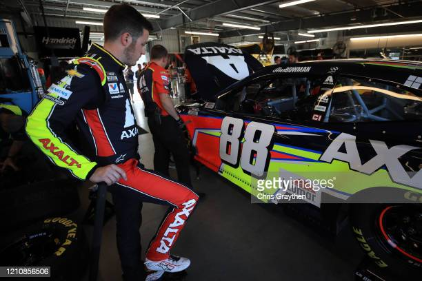 Alex Bowman driver of the Axalta Chevrolet stands in the garage area during practice for the NASCAR Cup Series FanShield 500 at Phoenix Raceway on...