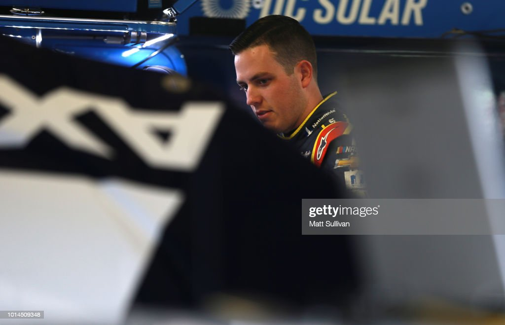 Alex Bowman, driver of the #88 Axalta Chevrolet, stands in the garage during practice for the Monster Energy NASCAR Cup Series Consmers Energy 400 at Michigan International Speedway on August 10, 2018 in Brooklyn, Michigan.