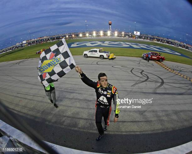 Alex Bowman driver of the Axalta Chevrolet waves the checkered flag after winning the Monster Energy NASCAR Cup Series Camping World 400 at...