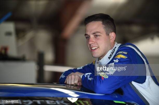 Alex Bowman driver of the Nationwide Chevrolet lays on his car in the garage during practice for the Monster Energy NASCAR Cup Series FireKeepers...