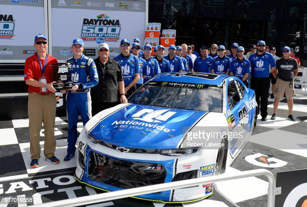 Alex Bowman driver of the Nationwide Chevrolet poses with team owner Rick Hendrick crew chief Greg Ives and crew members after winning the pole award...