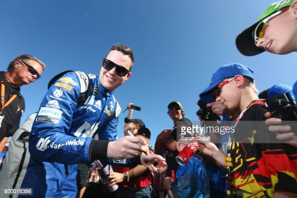 Alex Bowman driver of the Nationwide Chevrolet signs autographs prior to the start of the Monster Energy NASCAR Cup Series 60th Annual Daytona 500 at...