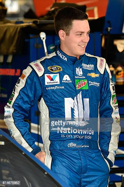 Alex Bowman driver of the Nationwide Chevrolet stands in the garage area during practice for the NASCAR Sprint Cup Series Hollywood Casino 400 at...