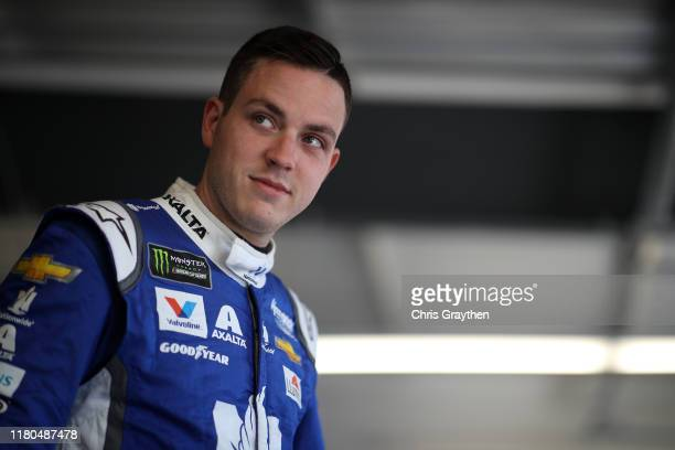 Alex Bowman driver of the Nationwide/Amazon Echo Auto Chevrolet stands in the garage area during practice for the Monster Energy NASCAR Cup Series...