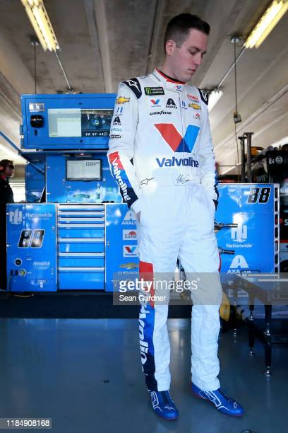 Alex Bowman driver of the Valvoline Chevrolet stands in the garage area during practice for the Monster Energy NASCAR Cup Series AAA Texas 500 at...