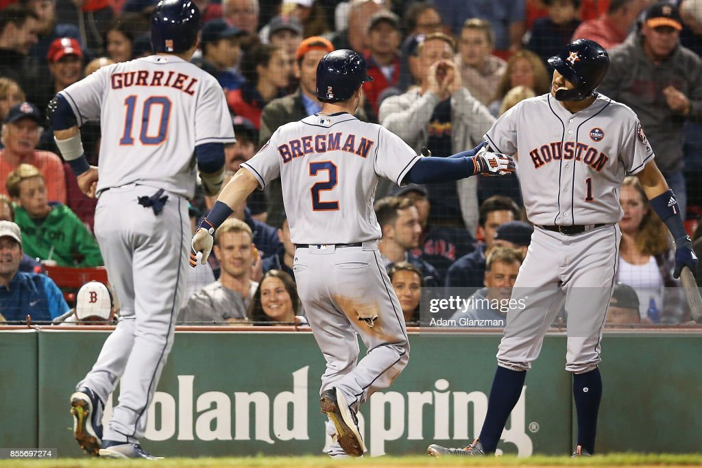 Alex Bregman #2 high fives Carlos Correa #1 of the Houston Astros after hitting a two-run home run in the fifth inning of a game against the Boston Red Sox at Fenway Park on September 29, 2017 in Boston, Massachusetts.