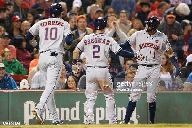 Alex Bregman high fives Carlos Correa of the Houston Astros after hitting a tworun home run in the fifth inning of a game against the Boston Red Sox...