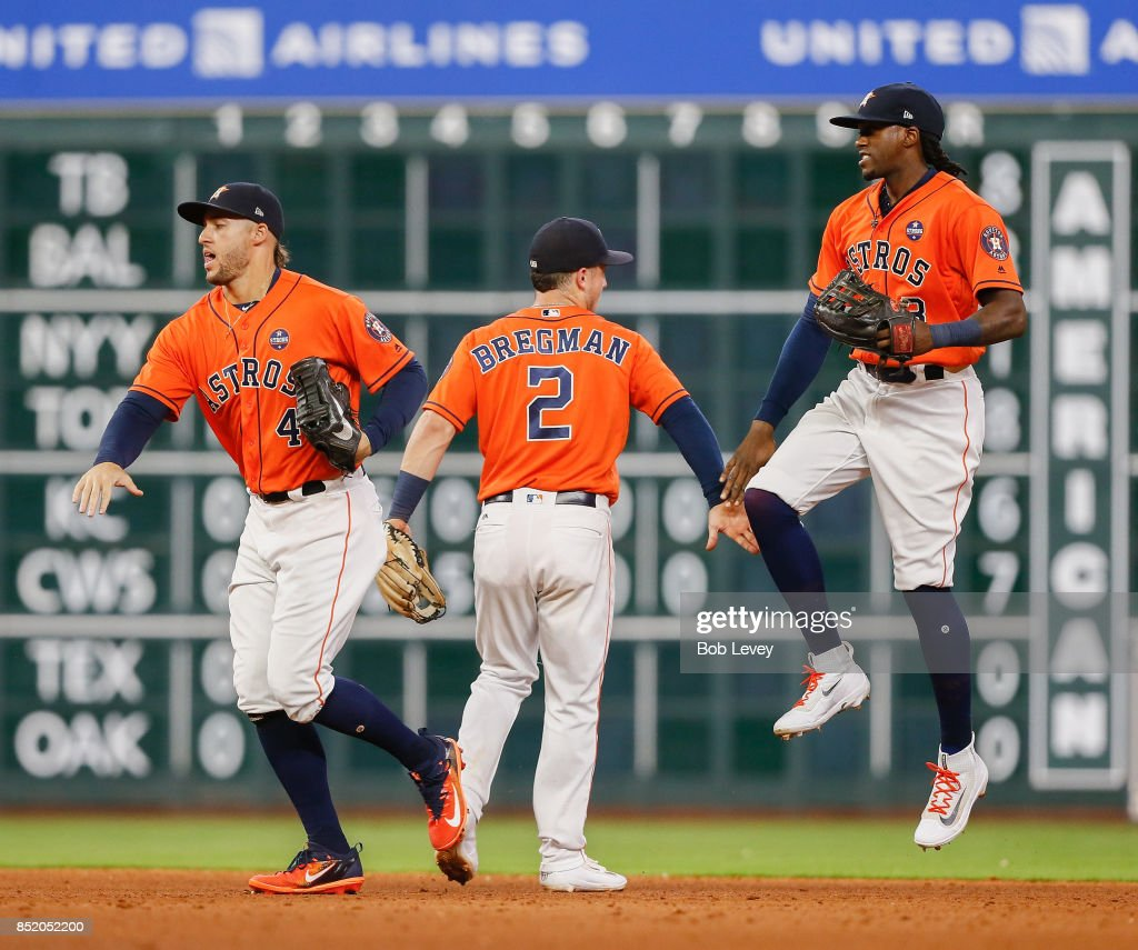 Alex Bregman #2 of the Houston Astros and George Springer #4 and Cameron Maybin #3 celebrate a 3-0 win over the Los Angeles Angels of Anaheim at Minute Maid Park on September 22, 2017 in Houston, Texas.