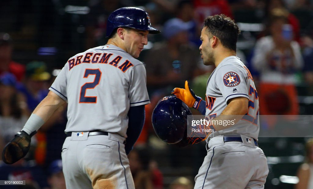Alex Bregman #2 of the Houston Astros and Jose Altuve #27 celebrate scores in the ring on Altuve two run home run in the seventh inning at Globe Life Park in Arlington on June 8, 2018 in Arlington, Texas.