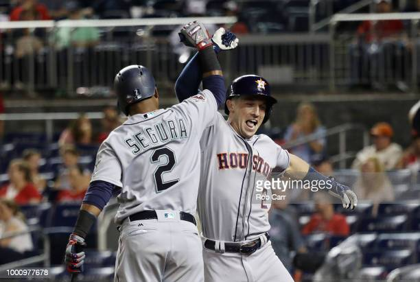 Alex Bregman of the Houston Astros and the American League celebrates with Jean Segura of the Seattle Mariners and the American League after hitting...