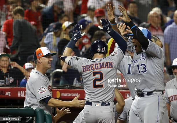 Alex Bregman of the Houston Astros and the American League celebrates with Manager AJ Hinch of the Houston Astros and the American League after...