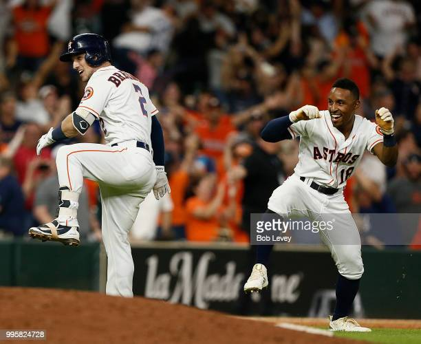Alex Bregman of the Houston Astros and Tony Kemp celebrate after wining in the eleventh inning against the Oakland Athletics at Minute Maid Park on...