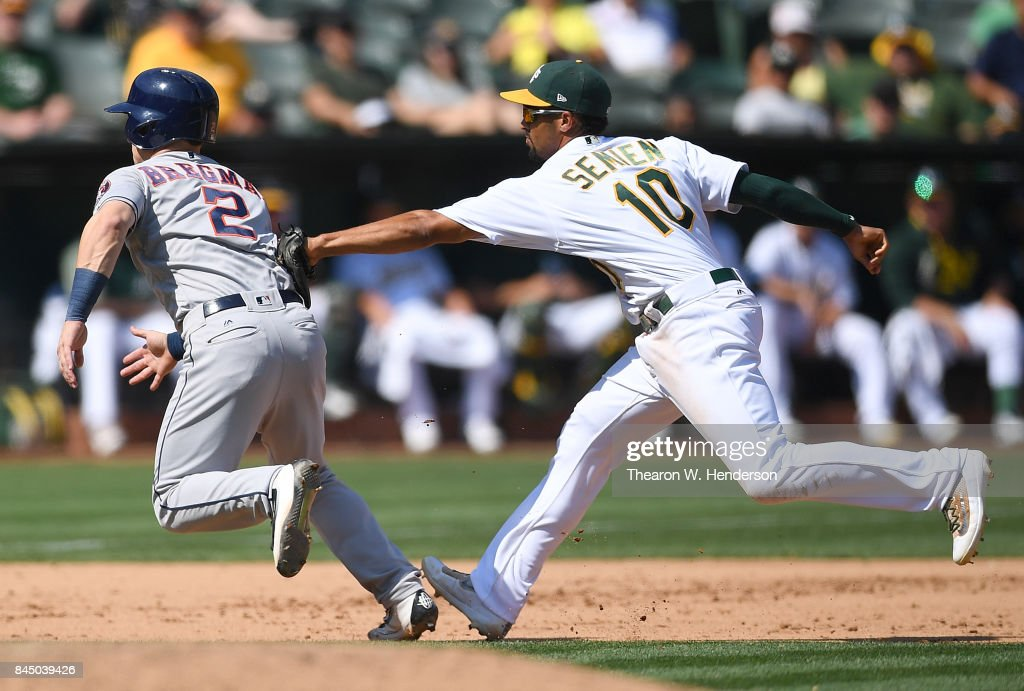 Alex Bregman #2 of the Houston Astros caught in a rundown gets tagged out by Marcus Semien #10 of the Oakland Athletics in the top of the fifth inning during game one of a doubleheader at Oakland Alameda Coliseum on September 9, 2017 in Oakland, California.